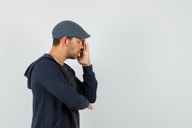Jonge man in t-shirt, jas, pet staande in denken pose met gesloten ogen en ziet er moe uit.