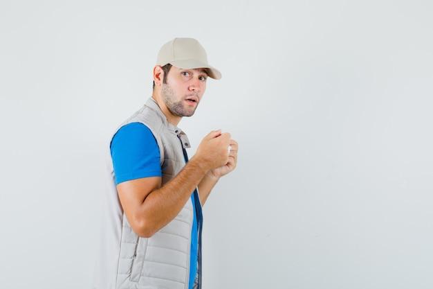Jonge man in t-shirt, jasje dat medisch masker probeert te dragen en er verstandig uitziet.