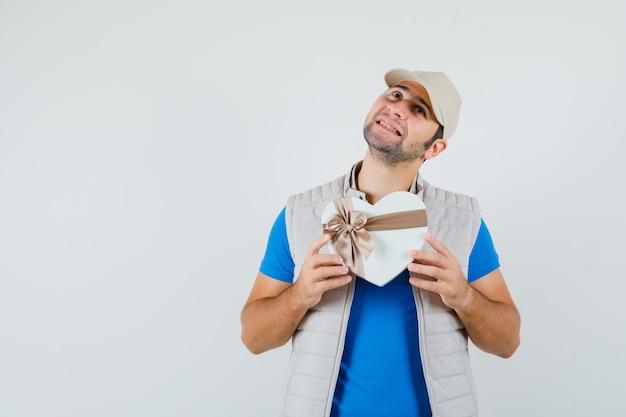 Jonge man in t-shirt, jasje met geschenkdoos en op zoek dromerig, vooraanzicht.