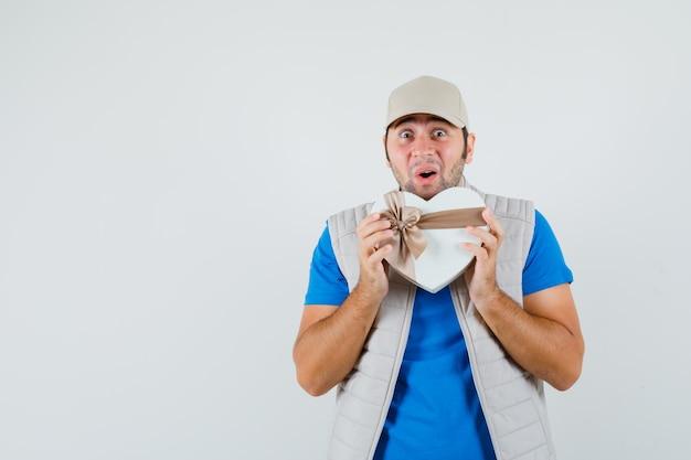 Jonge man in t-shirt, jasje met geschenkdoos en op zoek opgewonden, vooraanzicht.