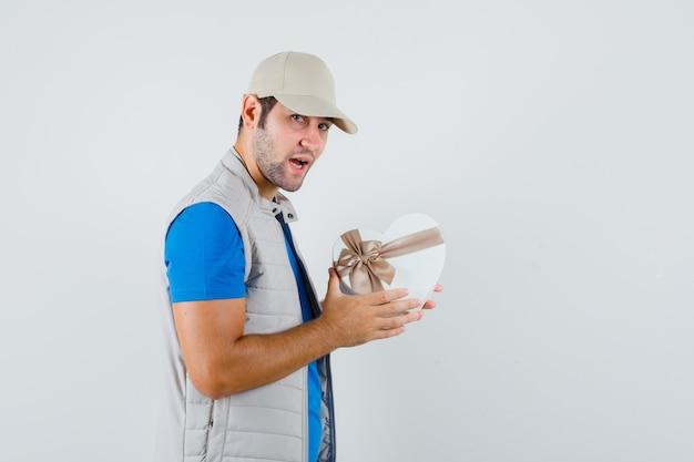 Jonge man in t-shirt, jasje met geschenkdoos en op zoek zelfverzekerd.