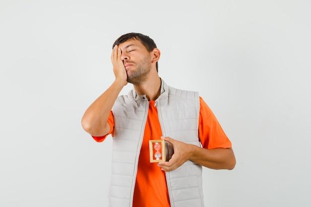Jonge man in t-shirt, jasje met zandloper met hand op gezicht en op zoek vergeetachtig, vooraanzicht.