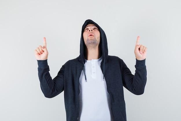 Jonge man in t-shirt, jasje naar boven en op zoek dankbaar, vooraanzicht.