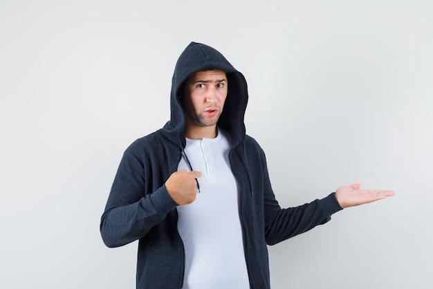 Jonge man in t-shirt, jasje naar zichzelf wijzend, palm opzij spreidend en verward kijkend, vooraanzicht.