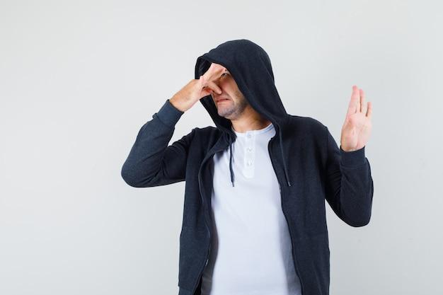 Jonge man in t-shirt, jasje neus dichtknijpen als gevolg van slechte geur en walgen, vooraanzicht op zoek.