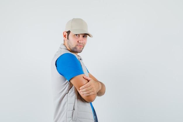 Jonge man in t-shirt, jasje permanent met gekruiste armen en op zoek zelfverzekerd.