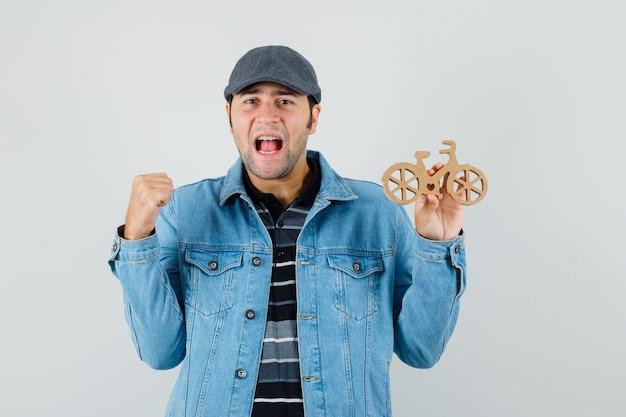 Jonge man in t-shirt, jasje, pet die winnaargebaar toont, houten speelgoedfiets houdt en gelukkig kijkt