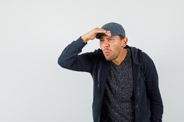 Jonge man in t-shirt, jasje, pet op zoek ver weg met hand boven het hoofd, vooraanzicht.