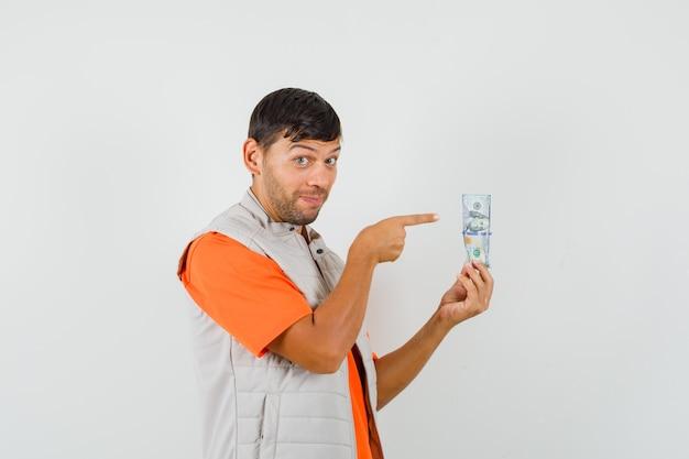 Jonge man in t-shirt, jasje wijzend op dollarbiljet en op zoek vrolijk, vooraanzicht.