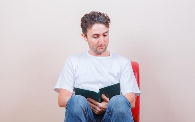 Jonge man in t-shirt, jeans die boek leest terwijl hij op een stoel zit