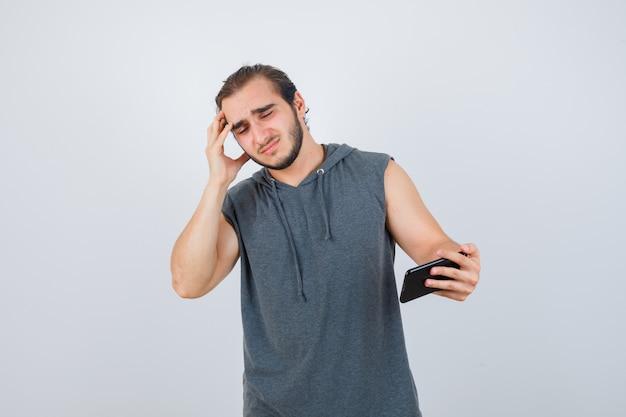 Jonge man in t-shirt met een kap die aan de telefoon kijkt, vingers op het hoofd houdt en boos, vooraanzicht kijkt.