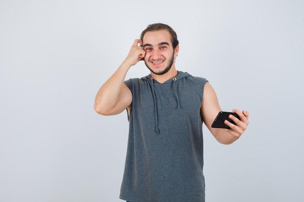 Jonge man in t-shirt met een kap die de telefoon in de hand houdt, de hand op het hoofd houdt en er vrolijk uitziet, vooraanzicht.