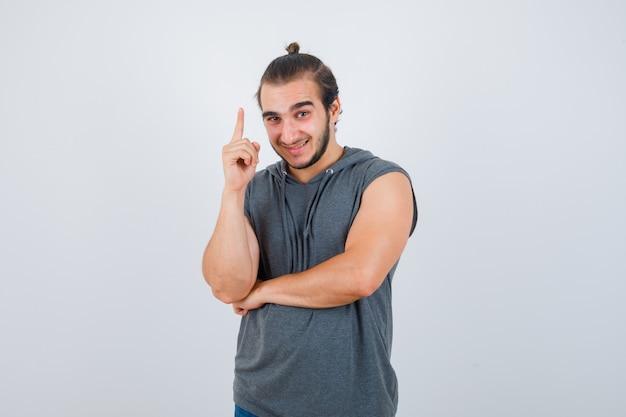 Jonge man in t-shirt met een kap die omhoog wijst en gelukkig, vooraanzicht kijkt.