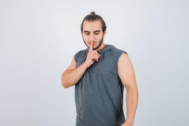 Jonge man in t-shirt met een kap met stilte gebaar en op zoek boos, vooraanzicht.