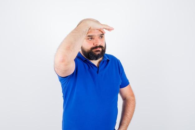 Jonge man in t-shirt met hand op voorhoofd en kijkend, vooraanzicht.