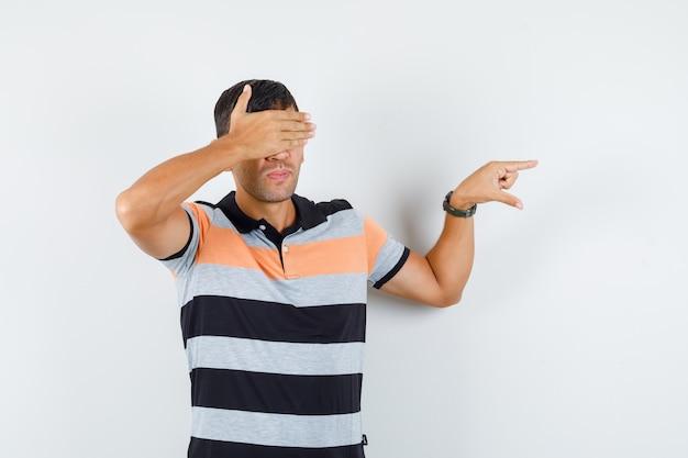 Jonge man in t-shirt met klein formaat bord, ogen bedekt