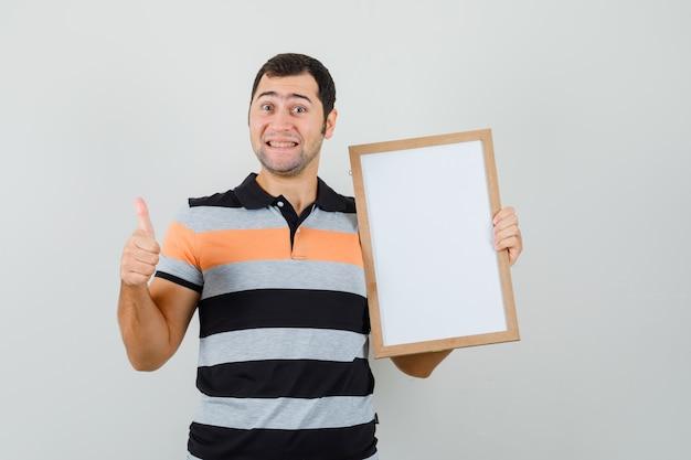 Jonge man in t-shirt met leeg frame terwijl duim opdagen en er gelukkig uitziet