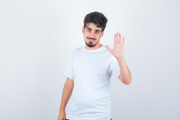 Jonge man in t-shirt met palm en ziet er schattig uit
