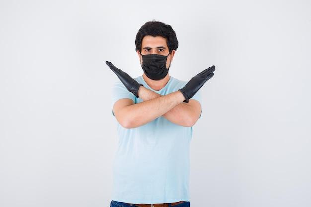 Jonge man in t-shirt met stopgebaar en angstig, vooraanzicht.