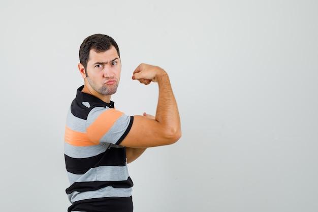 Jonge man in t-shirt met zijn armspieren en op zoek naar geweldige ruimte voor tekst