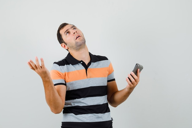 Jonge man in t-shirt opzoeken na het lezen van bericht en op zoek verontrust