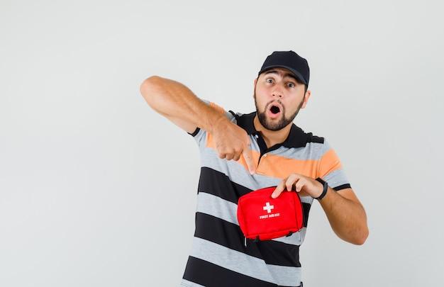 Jonge man in t-shirt, pet wijzend op ehbo-doos en op zoek verrast, vooraanzicht.