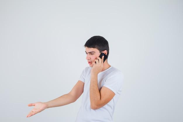 Jonge man in t-shirt praten op mobiele telefoon en kijken opgewonden, vooraanzicht.