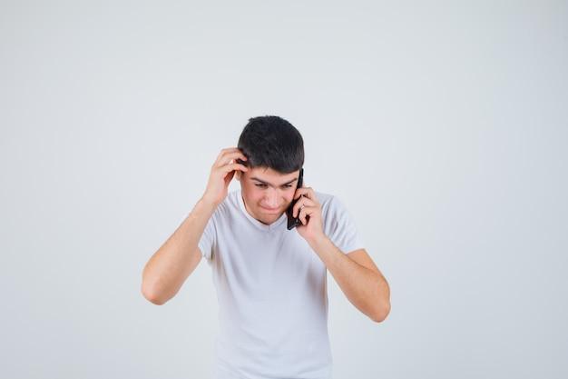 Jonge man in t-shirt praten op mobiele telefoon terwijl hoofd krabben en op zoek doordachte, vooraanzicht.