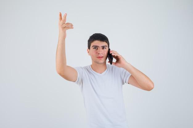 Jonge man in t-shirt praten over de mobiele telefoon terwijl hij zijn arm opheft en gefocust, vooraanzicht kijkt.
