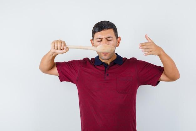 Jonge man in t-shirt proeverij maaltijd met houten lepel, vooraanzicht.