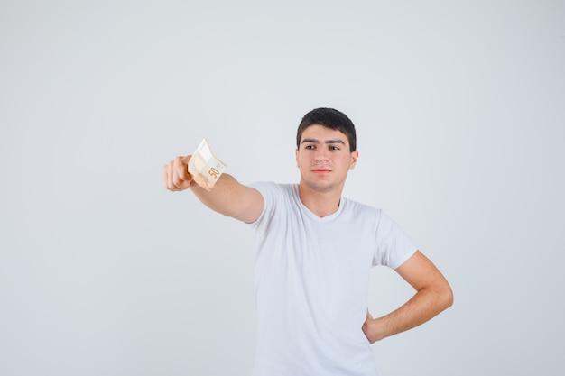 Jonge man in t-shirt strekt zich uit een hand met eurobankbiljet en kijkt zelfverzekerd, vooraanzicht.