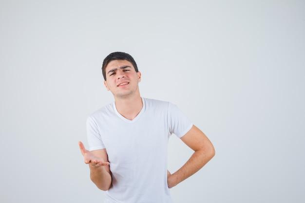 Jonge man in t-shirt uitrekken dient vragend gebaar in en kijkt zelfverzekerd, vooraanzicht.