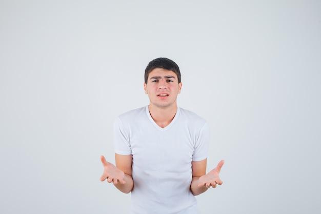 Jonge man in t-shirt uitrekken hand in vragend gebaar en op zoek opgewonden, vooraanzicht.