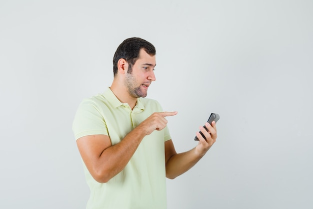 Jonge man in t-shirt wijzend op rekenmachine en kijkt verward, vooraanzicht.