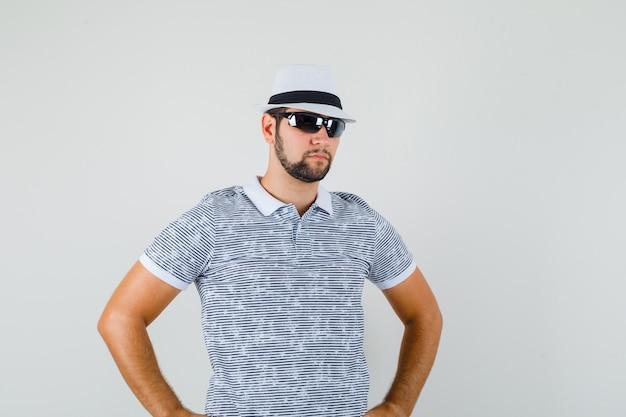 Jonge man in t-shirt, zonnebril permanent met handen op de taille en op zoek cool, vooraanzicht.