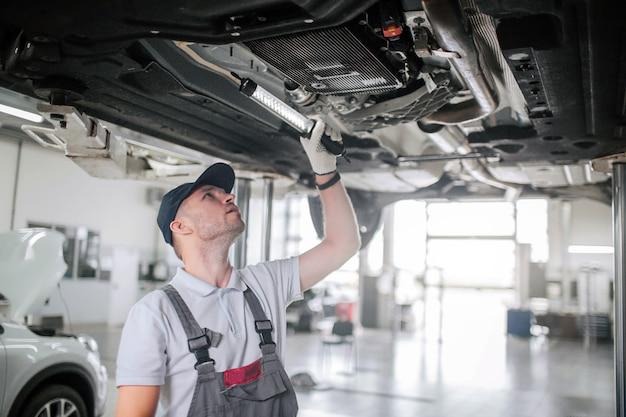 Jonge man in uniform staat onder auto en kijkt omhoog. hij houdt licht in de hand. guy is serieus en geconcentreerd. hij werkt.