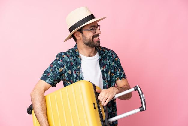 Jonge man in vakantie met reiskoffer en een hoed