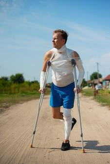 Jonge man in verbanden op krukken lopen op de weg op het platteland