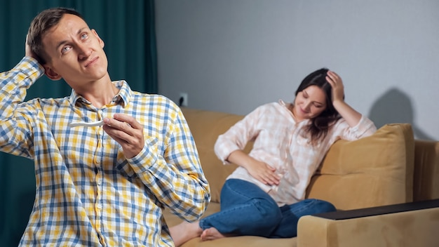 Jonge man in verbijstering kijkt naar een zwangerschapstest op de achtergrond van een gelukkige zwangere vrouw