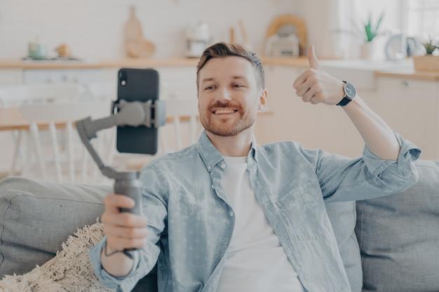 Jonge man in videogesprek die zijn tevredenheid uitdrukt, gimbal vasthoudt met telefoon bevestigd, duim omhoog gebaar maakt en het aan de camera laat zien terwijl hij op de bank zit, onscherpe achtergrond