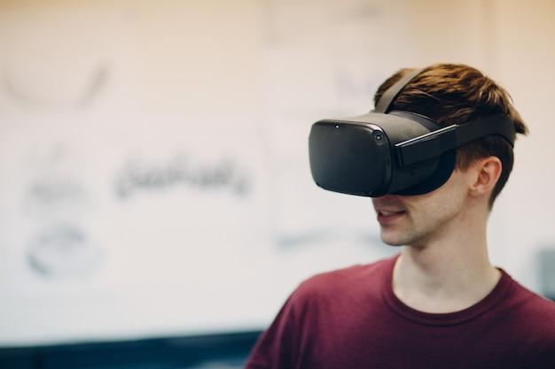 Jonge man in virtual reality bril, vr bril headset met joystick