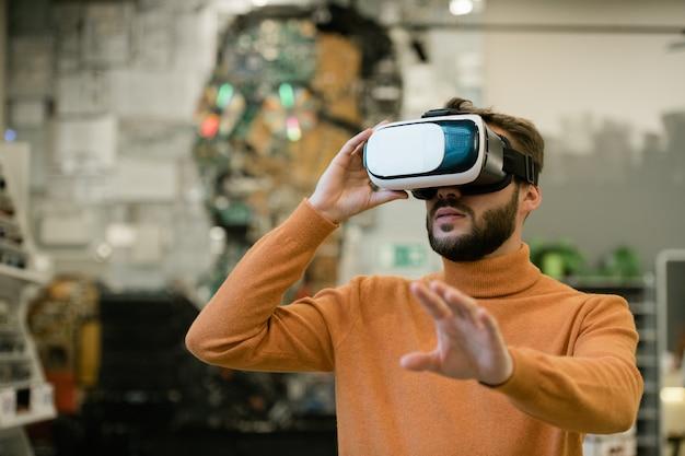Jonge man in virtual reality headset arm uitrekken terwijl staande voor display en aanraken