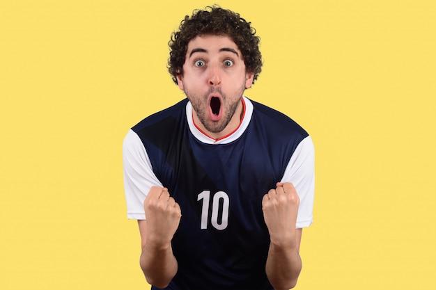 Jonge man in voetbal uniforme voetbal schreeuwen terwijl zijn team winnen.