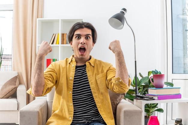 Jonge man in vrijetijdskleding blij en opgewonden met gebalde vuisten zittend op de stoel in lichte woonkamer living