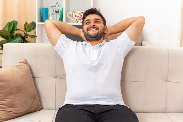 Jonge man in vrijetijdskleding blij en positief glimlachend vrolijk ontspannen zittend op een bank in lichte woonkamer in