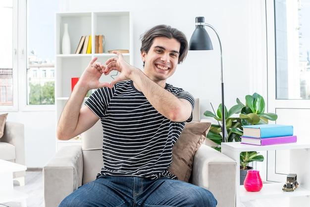 Jonge man in vrijetijdskleding, blij en positief, hartgebaar makend met vingers zittend op de stoel in lichte woonkamer