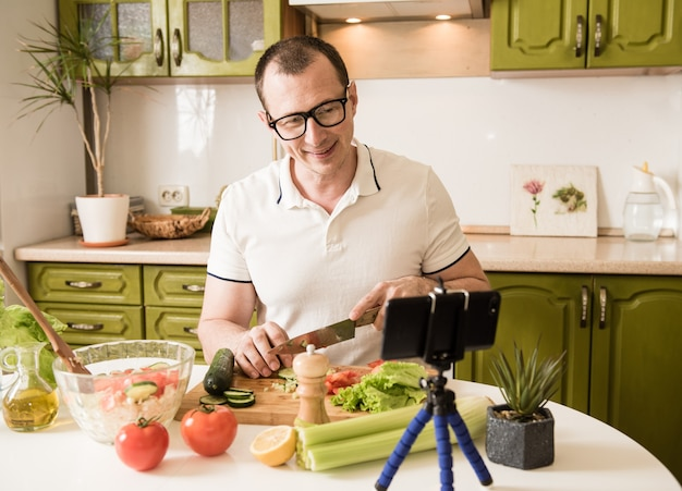 Jonge man in vrijetijdskleding camera kijken en glimlachen zittend in de keuken thuis