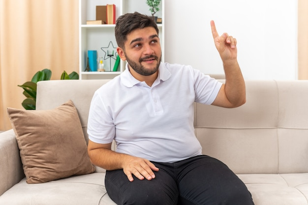 Jonge man in vrijetijdskleding die blij en verrast opkijkt en wijsvinger laat zien met een nieuw goed idee zittend op een bank in een lichte woonkamer