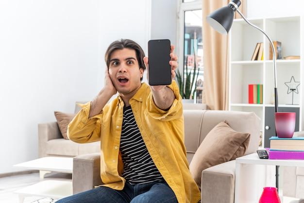 Jonge man in vrijetijdskleding die een smartphone laat zien die verbaasd en verrast op de stoel zit in een lichte woonkamer