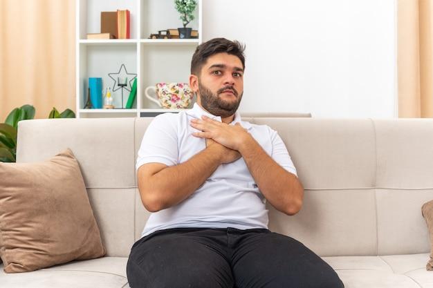 Jonge man in vrijetijdskleding die er bezorgd en verward uitziet met handen op zijn borst zittend op een bank in lichte woonkamer